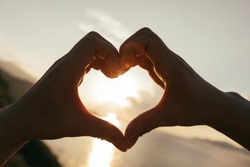 Two hands making heart shape in sky