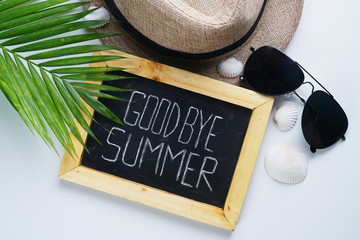 Goodbye Summer Text. Sunglasses, Fedora Hat, Palm Leaf, Sea Shells and Blackboard Room for Text. Flat Lay Traveling Holiday Vacation Background