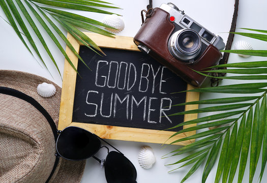 Goodbye Summer Text. Sunglasses, Fedora Hat, Palm Leaf, Camera, Sea Shells and Blackboard Room for Text. Flat Lay Traveling Holiday Vacation Background
