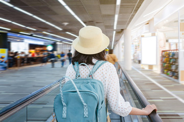 Beautiful young tourist girl wearing cream hat with green backpack on speedwalk in international airport to travel on weekends,motion blur,Travel departure concept.