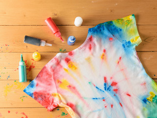 T-shirt painted in tie dye style on a brown wooden table.