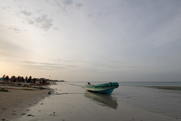 Beached and anchored small fishing boat at sunset on Nilaveli beach in Trincomalee Sri Lanka Asia