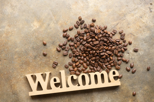 Decorative letters word welcome with coffee bean on texture background for cafe.