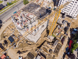 yellow tower crane at construction site. development of city residential area. aerial top view