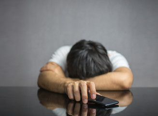 Man waiting for a phone call on table, face down