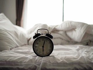 alarm clock on the bed in bedroom on morning