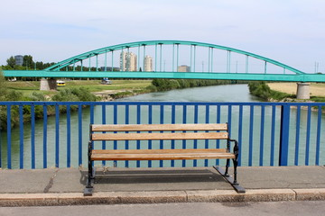 Public wooden bench with wrought iron legs mounted on asphalt road with old green metal arched railway bridge on two strong concrete pillars covered in stone over mighty river in background