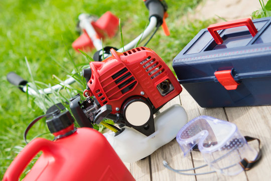 a set of tools for the care of green lawn, red chainsaw, fuel cans, a tool for adjustment.