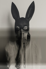 young attractive woman in bunny mask showing quiet sign with her eyes closed