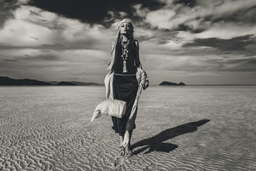 beautiful young stylish woman walking on low tide at sunset. black and white. fashion concept
