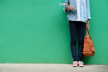 Student girl holding books and school bag standing over green wall background with copy space, education, back to school concept