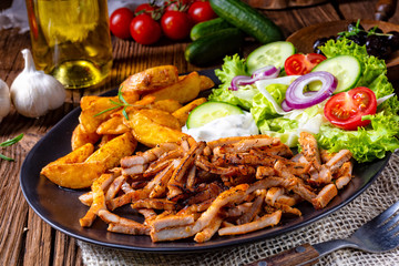 Rustic gyros plate it green salad and potato wedges