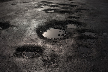 pothole in the road looking like alien craters