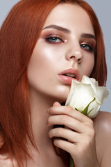 Beautiful red-haired girl with a classic make-up and rose in her hands. Beauty face. Photo taken in studio