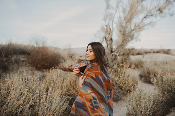 Back side of boho woman with windy hair in the desert nature, turning her head and smiling .  Artistic photo of young hipster traveler girl in gypsy look, in Coachella Valley in a desert vall