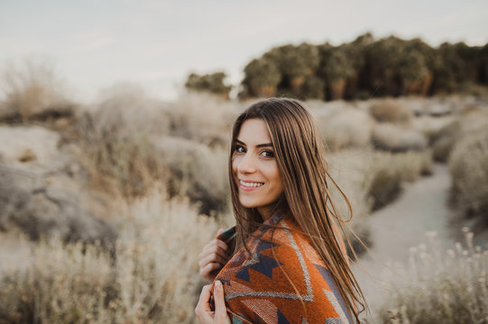 Smiling beautiful hipster traveler girl in gypsy look in desert nature.  Artistic photo of young hipster traveler girl in gypsy look, in Coachella Valley in a desert valley in Southern California.