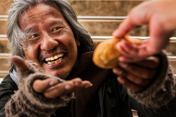 Homeless male with happy face showing hands to recieve bread from donator hand Wall mural