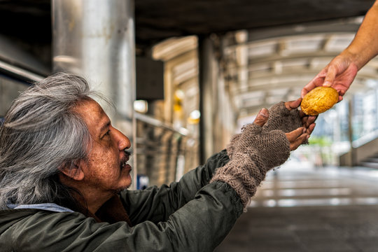 Homeless male with happy face showing hands to recieve bread from donator hand