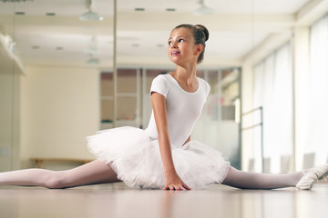 Portrait of a beautiful girl, in a dance school wearing a white tutu, she trains alone to learn new dance steps. Concept of: ambition, education, elegance and love for the dance.