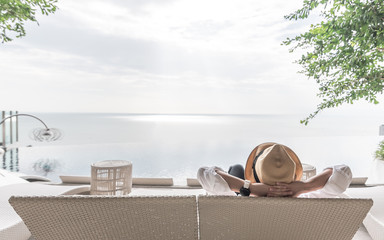 Relaxation holiday vacation of businessman take it easy resting on beach chair at swimming pool poolside beachfront resort hotel with sea or ocean view and summer sunny sky