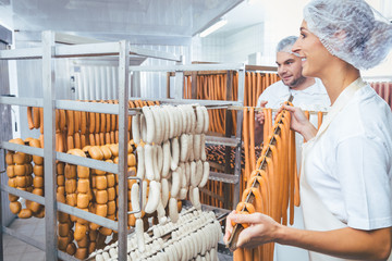 Woman working in butchery putting sausages on beam in rack for smoking