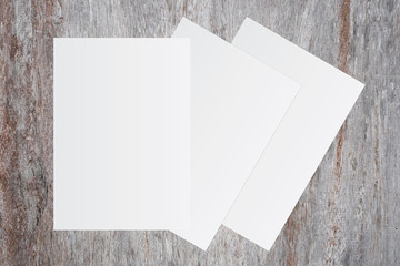 Blank white paper on brown wooden background for text input.