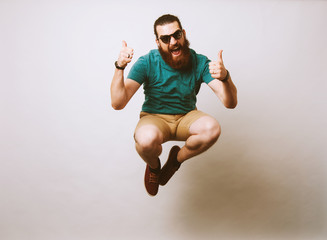 Man jumping and showing thumbs up Wall mural