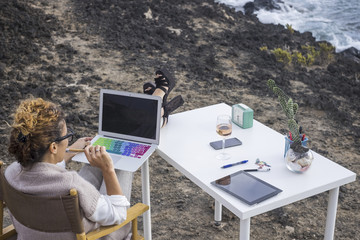 alternative office business place for elegant manager woman caucasian working with technology modern laptop just in front of the ocean. phone and tablet on the desktop with ocean view. workstation