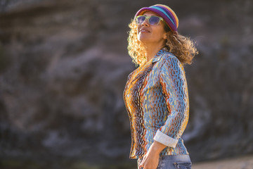 cheerful happy attractive middle age caucasian woman smile and look in the air enjoying the nice weather and the sun. happiness in outdoor leisure activity and coloured dress like hippy