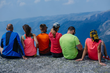 Back view of group six friends hikers relaxing together after intensive climbing. Team travelers sitting on peak stone and enjoying mountains view. Norway trip. Travel and adventures concept