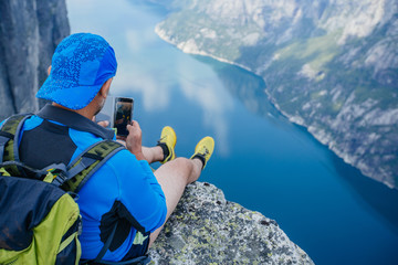 Sportive man in blue sportswear with yellow backpack making photo on smart phone and enjoying the view with blue water fjord from a mountain in Norway. Top view.