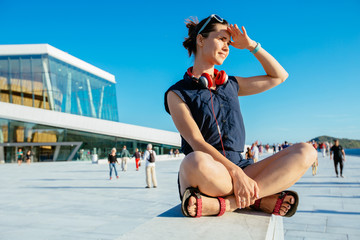 Young hipster woman traveler with red headphones resting on border after walking in Oslo city over Opera House urban background, happy, smiling, looking in sunset.
