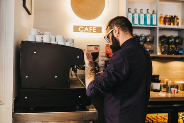 Barista making coffee with machine in cafeteria