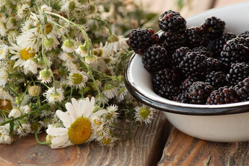 Ripe blackberry in an enamel  dish, and garden flowers, on old wooden table.
