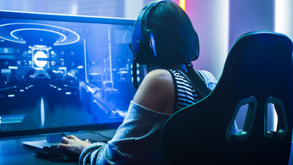 Shot of the Beautiful Pro Gamer Girl Playing in First-Person Shooter Online Video Game on Her Personal Computer. Casual Cute Geek wearing Glasses and Headset. Neon Room. eSport Cyber Games Event.