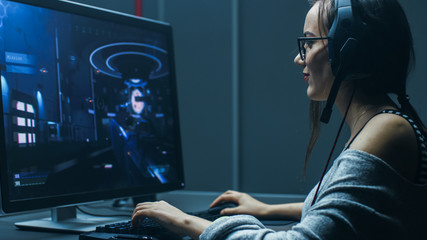 Shot of the Beautiful Professional Gamer Girl Playing in First-Person Shooter Online Video Game on Her Personal Computer. Casual Cute Geek wearing Glasses and Talking into Headset. In Gaming Club.