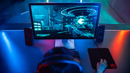 High-angle Shot of the Professional Gamer Playing in First-Person Shooter Online Video Game on His Personal Computer. Room Lit by Neon Lamps in Retro Arcade Style.