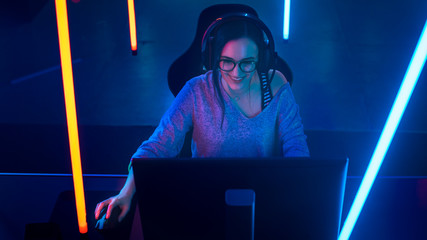 High Angle Shot of the Beautiful Friendly Pro Gamer Girl Playing in Online Video Game and Streaming it, Wearing Headset Talks with Her Fans and Team into Headphones. Background Cool Neon Retro Colors.