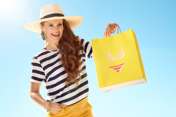 woman against blue sky showing yellow shopping bag with bikini