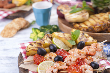 Picnic with grilled food. Shrimp and grilled vegetables with lime and olives. Delicious summer lunch and plastic dishes. Top view