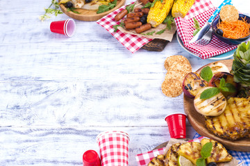 Picnic with grilled food. Sausages and corn on a barbecue. Delicious summer lunch and plastic dishes. Top view