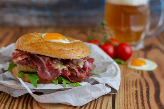 Bagel sandwich with turkey, bacon, ruccola, cheese, tomatoes and quail egg on the wooden background. Bagel burger with beer on the background