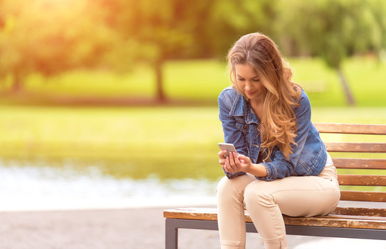 Young woman sitting on bench and use her phone in park