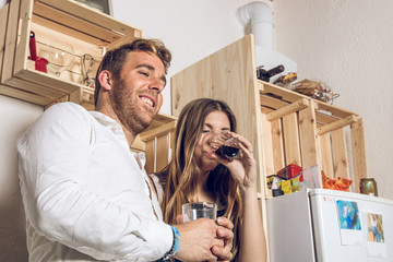 Happy young couple drinking wine in the kitchen at home