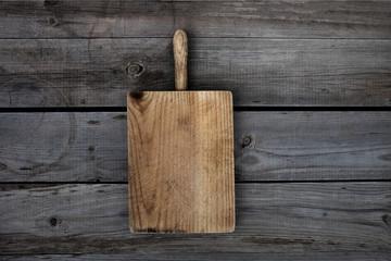 Wooden cutting board on dark background. Old grunge desk