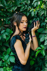 Portrait of young sexy brunette with black grapes.