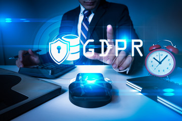 The abstract image of the businessman point to the GDPR hologram on smartphone in office. the concept of data, communications, privacy, internet of things and GDPR.