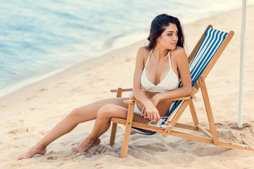attractive girl holding sunglasses and sitting on beach chair near the sea