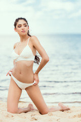 brunette woman in white swimsuit relaxing on beach at sea