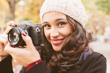 Young beautiful woman with a woolen cap taking pictures with a retro camera in the city in autumn